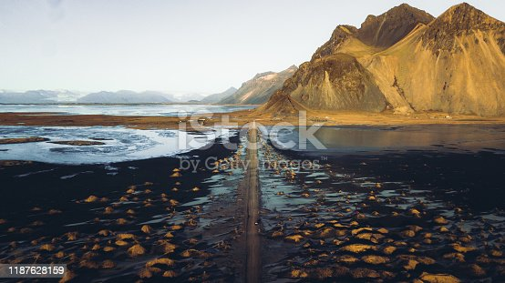 Drone photo of a car driving though the picturesque road at Stokksnes black sand beach with huge dunes and scenic mountains during bright winter sunrise
