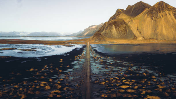 Aerial view of a car driving though dramatic landscape with sand dunes, mountains and sea in East Iceland stock photo