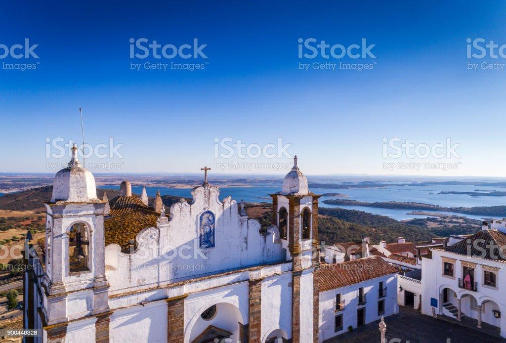 Luftaufnahme der Kirchenfassade im historischen Dorf von Monsaraz im Alentejo mit dem Alqueva-Stausee im Hintergrund – Foto