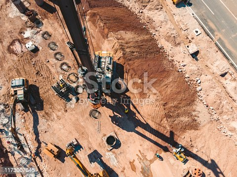 Aerial view of a construction site with diggers, bulldozers, mobile cranes...