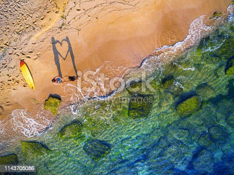 Aerial view of a couple having fun on a beach and making heart with hands