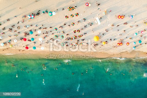 Aerial view of a crowded beach, umbrellas and people on the sand