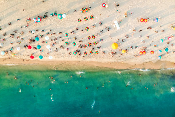 Aerial view of a crowded beach, umbrellas and people on the sand Aerial view of a crowded beach, umbrellas and people on the sand miami beach stock pictures, royalty-free photos & images