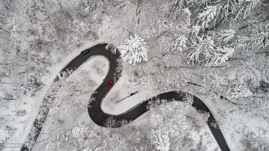 Aerial view of a curvy road in winter Aerial view of a curvy road in winter with lot of snow Above Stock Photo