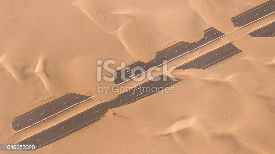 531886585 istock photo Aerial view of a desert road being run over by sand dunes. 1046053020