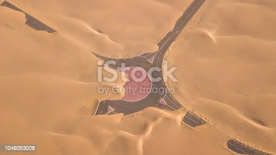 531886585 istock photo Aerial view of a desert road being run over by sand dunes. 1046053028