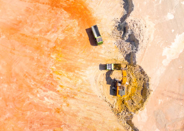 Aerial view of a excavator loading a truck in open cast mine or on construction site. Heavy industry from above. Industrial background from drone. stock photo