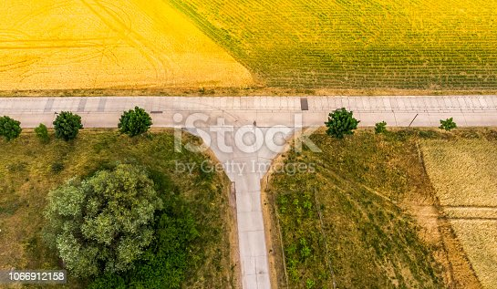 1095367134 istock photo Aerial view of a field path between fields and meadows, which meets a yellow rapeseed field 1066912158