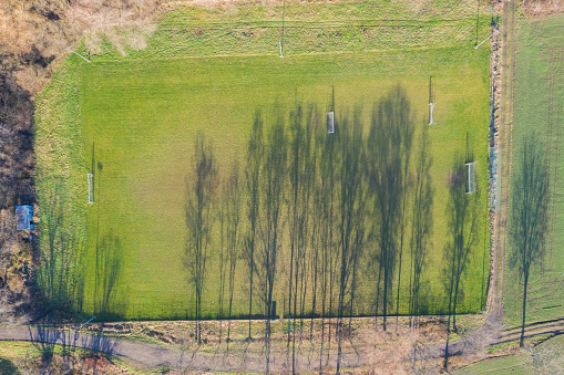 Aerial view of a football field in a village. A shadow from the trees falls on the field.