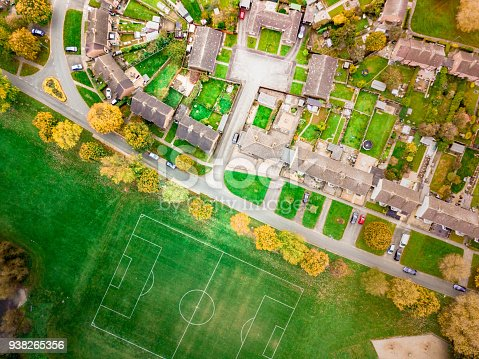istock Aerial view of a football pitch, fields and homes on public recreation ground. 938265356