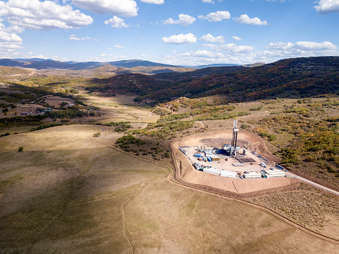 Heroic scene of a fracking drill rig set in the pristine Colorado Rockie Mountains in the Fall