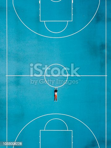 Aerial view of a girl hanging in a basketball court. conceptual realism trend