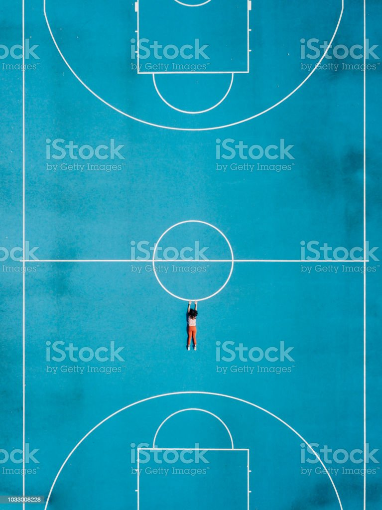 Aerial view of a girl hanging in a basketball court stock photo