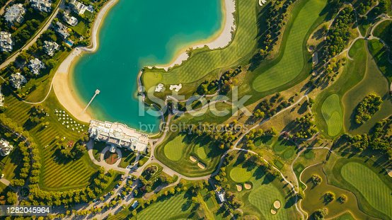 Drone point of view of a golf golf club with sand pits, trees, lakes.