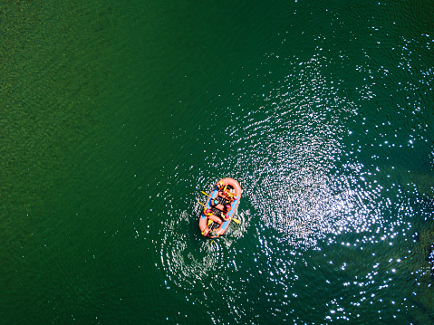 Drone point of view of a group men and women rafting in a calm river