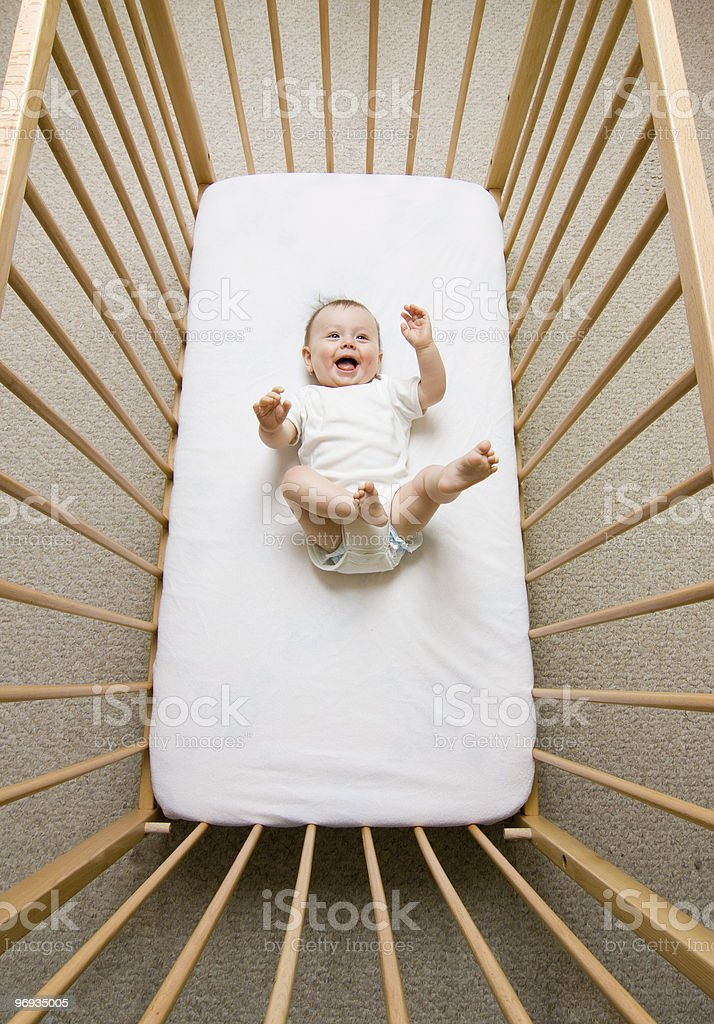 Aerial view of a happy baby girl in a wooden crib royalty-free stock photo