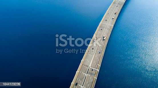 Aerial view of a high way road on the bridge over blue water