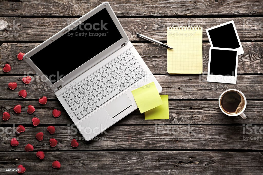 Aerial view of a laptop placed on an old wooden table stock photo