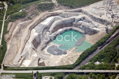 Aerial view of a large quarry site with a considerable amount of detail. Two mining trucks are climbing out of the pit, a large sorting and crushing operation is in the top right, a railroad runs down the right of the frame and a highway borders the bottom. Shot from the open window of a small airplane.