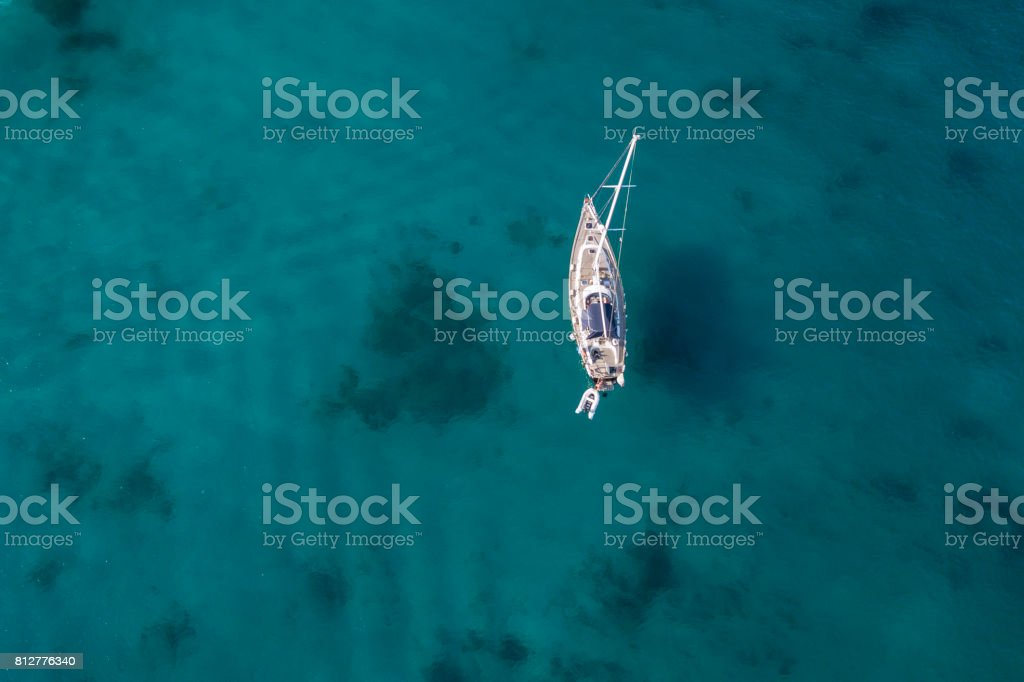 Aerial view of a little yacht on amazing beach with a turquoise and transparent sea. Emerald Coast, Sardinia, Italy. stock photo