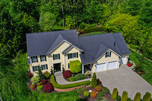 Aerial view of a yellow modern American craftsman home with lush landscaping, set among a forest of trees