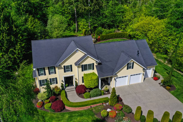 Aerial View of a Modern American Craftsman Style House Exterior Aerial view of a yellow modern American craftsman home with lush landscaping, set among a forest of trees drone point of view stock pictures, royalty-free photos & images