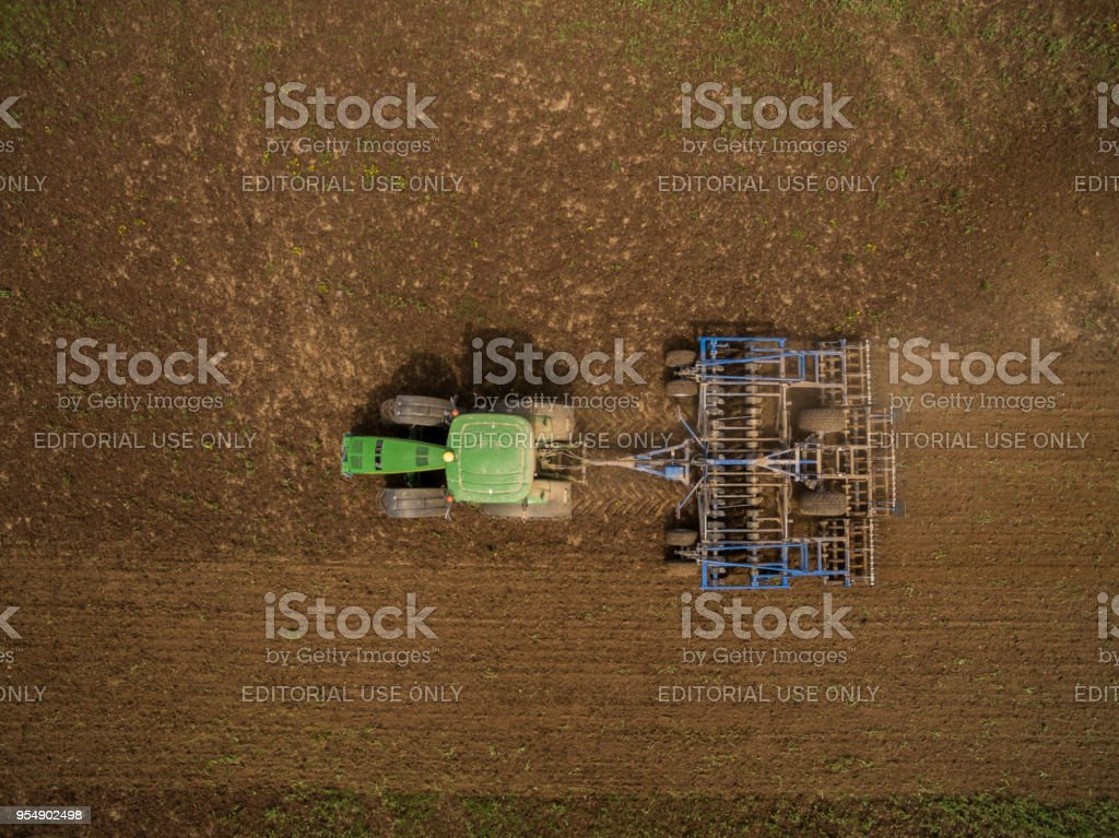 Luftaufnahme des modernen John Deere Traktor zieht einen Pflug Anhänger in einen landwirtschaftlichen Bereich – Foto