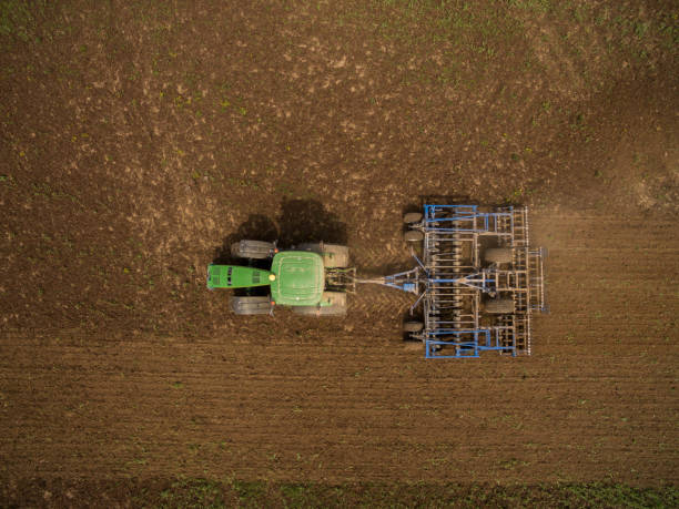 luftaufnahme des modernen john deere traktor zieht einen pflug anhänger in einen landwirtschaftlichen bereich - aerial view soil germany stock-fotos und bilder