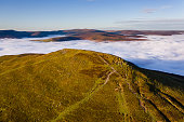 Aerial view of a mountain peak rising above a sea of low cloud and fog in the valley below (Sugar Loaf, Brecon Beacons, Wales)