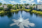 Aerial view of a townhouse complex with a pond and fountain in a Chicago suburban neighborhood in summer.