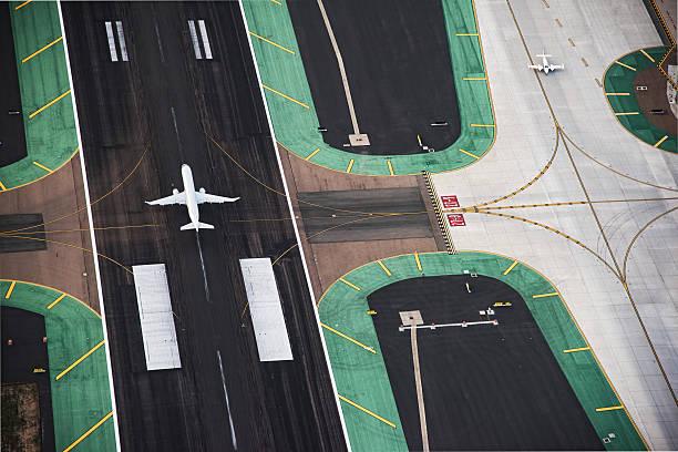 vista aérea de un avión de pasajeros en la pista de aterrizaje - aterrizar fotografías e imágenes de stock