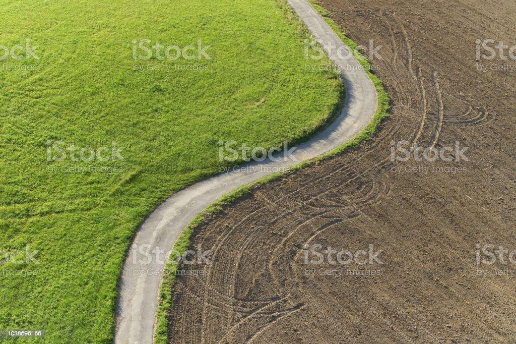 在草甸和領域之間的路徑鳥瞰。 - 免版稅切半圖庫照片