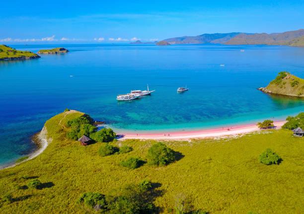 Luftaufnahme eines rosa Strandes in Flores, mit einem Touristen und einem Yatch – Foto