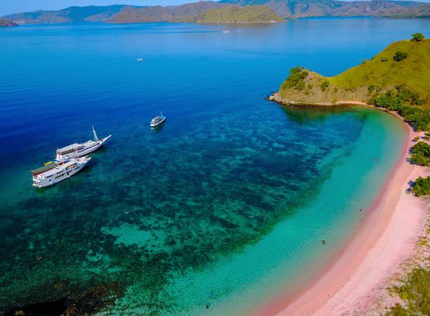 Luftaufnahme eines rosa Strandes in Flores, mit einem Touristen und einem Yatch. – Foto