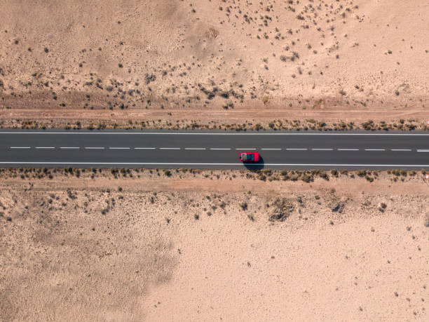 Aerial view of a red car in the desert valleys of the island of Lanzarote, Canary Islands, Spain stock photo