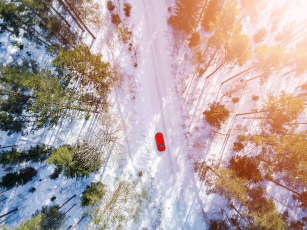 Aerial view of a red car on white winter road. Winter landscape countryside. Aerial photography of snowy forest with a red car on the road. Captured from above with drone. Quadcopter. Birds eye view. Soft lighting stock photo