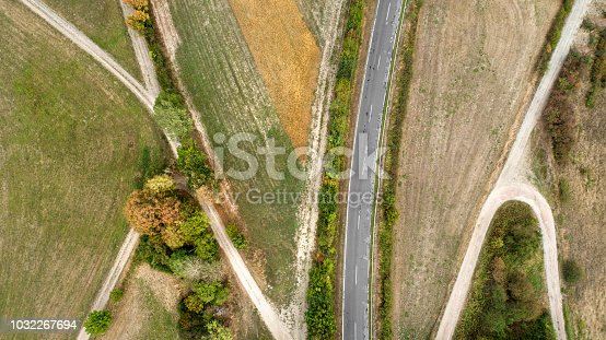istock Aerial view of a road and tracks through fields 1032267694
