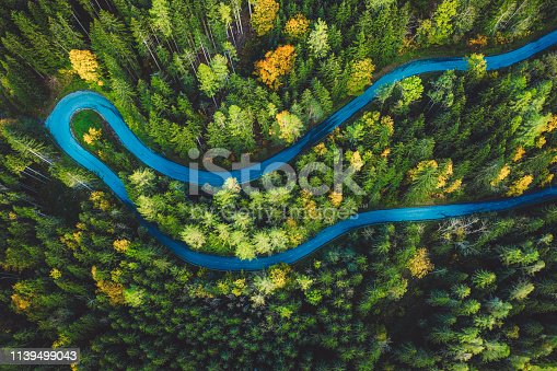Aerial footage, drone shoot, curvy road in Slovenian Alps, leading up the mountain. Beautiful scenery, spring forest, lonely road.