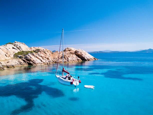 """veduta aerea di una barca a vela di fronte all'isola di mortorio in sardegna. spiaggia incredibile con un mare turchese e trasparente. costa smeralda, sardegna, italia. t""""n - sardegna foto e immagini stock"""
