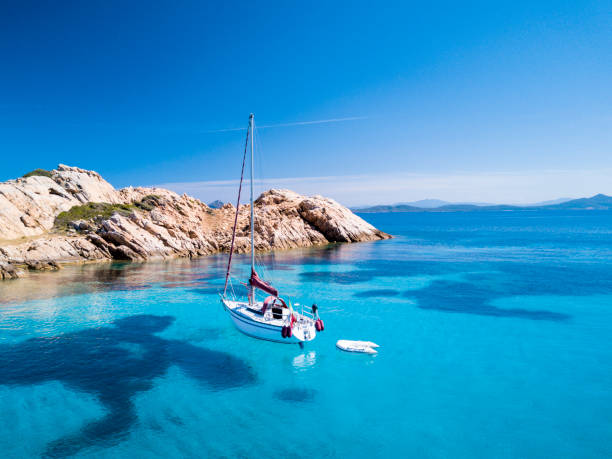 """aerial view of a sail boat in front of mortorio island in sardinia. amazing beach with a turquoise and transparent sea. emerald coast, sardinia, italy.""""t""""n - sardegna foto e immagini stock"""