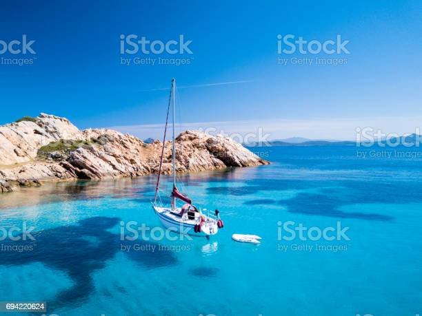 """Aerial view of a sail boat in front of Mortorio island in Sardinia. Amazing beach with a turquoise and transparent sea. Emerald Coast, Sardinia, Italy.""""t""""n"""
