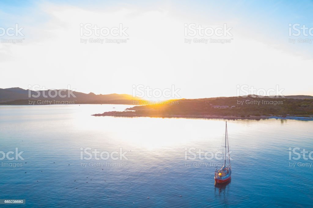 Aerial view of a sailboat in a bay of the Emerald coast at sunset in Sardinia, Italy. foto de stock royalty-free