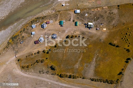 Aerial view of a settlement in the Altai Mountains with small houses for indigenous people and tourists, ail for nomadic living with yellow grass and trees at indian summer.