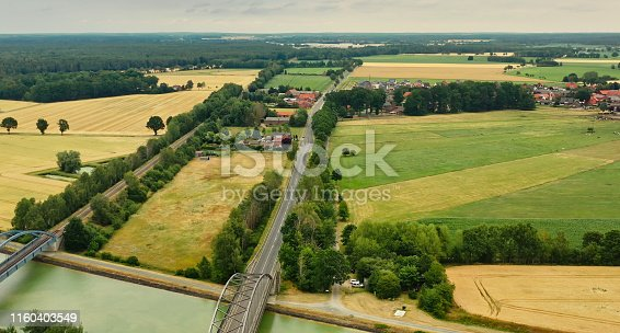 1095367134 istock photo Aerial view of a small German village in the flat region of northern Germany with pastures, arable land and cows, country road and railway on the side 1160403549