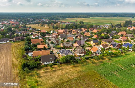 1095367134 istock photo Aerial view of a small village in northern Germany with large arable land at the edge of the village 1022336794