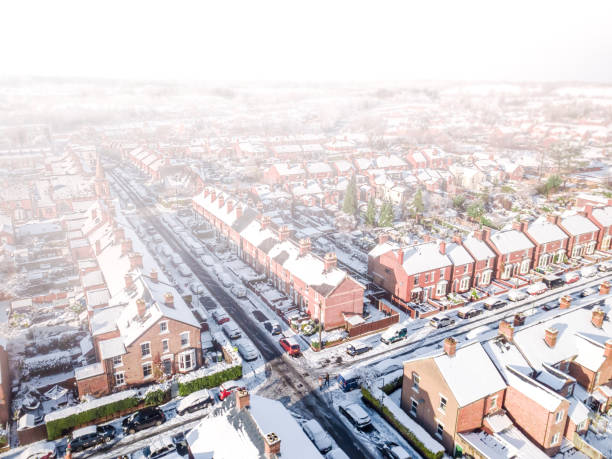Aerial view of a snow blizzard covering a traditional housing suburbs in England. stock photo