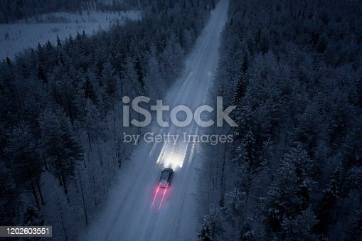 Aerial view of a snow road going through in the snow covered forest in Finland