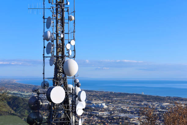 aerial view of a telecommunication tower, satellite dish, network repeaters, base transceiver. antenna for wireless network. cellular station for smart city connect and coastline as background. - ricetrasmettitore foto e immagini stock