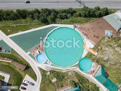 istock Aerial view of a tourist recreation center in with three swimming pools and wooden sun loungers on nature in the Altai mountains on a sunny warm day. Rest, tourism and vacation. 1171076852