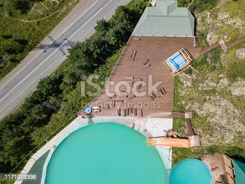 istock Aerial view of a tourist recreation center in with two swimming pools and wooden sun loungers on nature in the Altai mountains on a sunny warm day. Rest, tourism and vacation. 1171073398